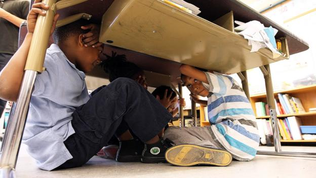 School children take cover under desks during an earthquake drill. (Getty)