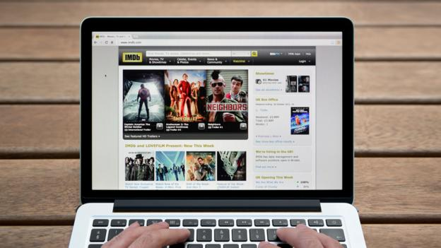 A laptop shows the front page of IMDb