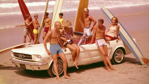 A group of young men and women lean or sit on a mid-60s Ford Mustang convertible