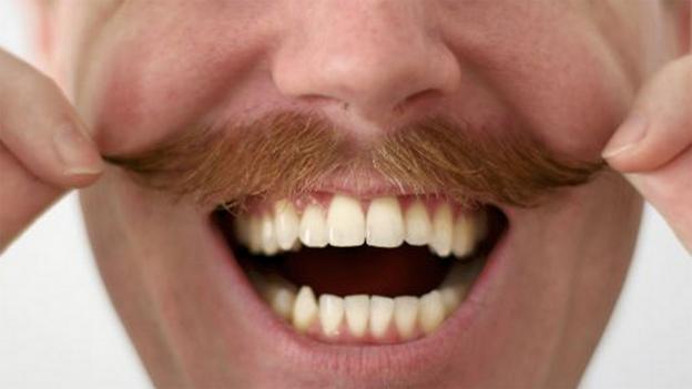A smiling man twirls his moustache
