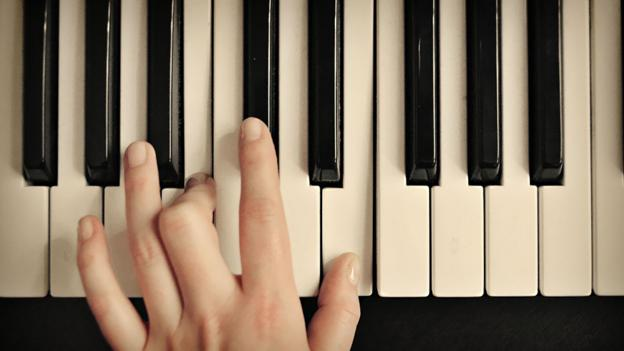 A hand plays a piano