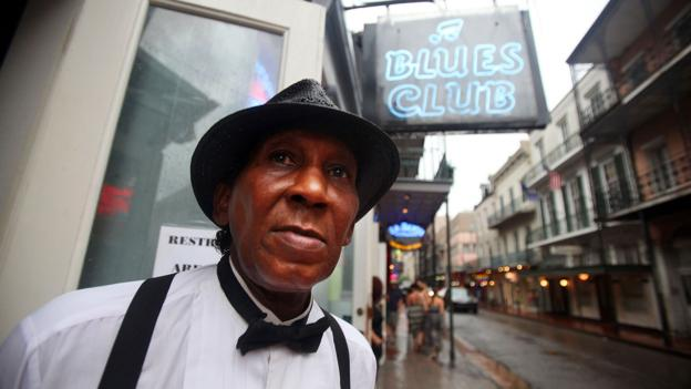 Doorman and musician Skip Thompson keeps watch on Bourbon Street (Credit: Mario Tama/Getty)