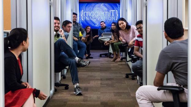 """Pankaj Arora, at back in blue, in Microsoft's """"hallway of knowlege"""". (Microsoft)"""