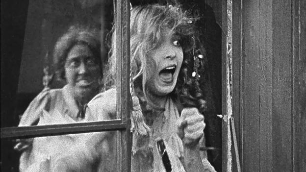 Fotograma de 'El nacimiento de una nación', una mujer con cara aterrada por la amenaza de un actor pseudonegro