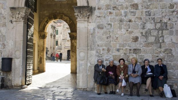 Women sitting by Dubrovnik's city walls (Credit: Credit: Santiago Urquijo/Getty)