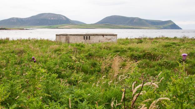 An abandoned pillbox looks over calm waters (Credit: Credit: Amanda Ruggeri)
