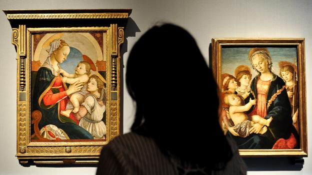A visitor looks at two paintings by Italian Renaissance painter Sandro Botticelli at Palazzo Strozzi in Florence