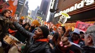 Fast-food workers in several cities across the US stage a 24-hour strike in protest against low wages.
