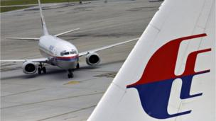 Shares in Malaysia Airlines plunge 18% to a record low as the search for a missing jet continues for a third day.