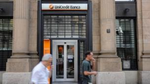 UniCredit, Italy's biggest bank by assets, reports a record 14bn-euro (£11.7bn; $19bn) loss for 2013 and plans to cut 8,500 jobs.