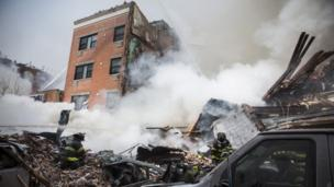 Two women die and 22 other people are injured as a gas leak sparks an explosion which razes two buildings in New York City.