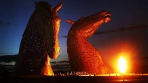 The Kelpies, a massive new art installation overlooking the M9 near Falkirk, are lit up as part of a pyrotechnic launch event.