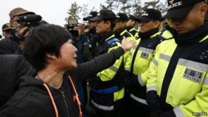 Families of passengers on a sunken South Korean ferry protest angrily over the rescue operation, scuffling with police on Jindo island.