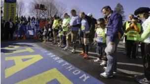 Boston marathon competitors observe a moment's silence ahead of the start of the race, in tribute to those killed and injured in a bomb attack last year.