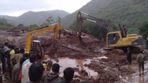 Rescue workers in western India race to locate survivors of a landslide that has claimed at least 23 lives and buried some 40 homes.