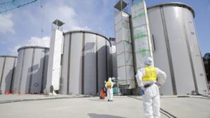 A group of workers decommissioning the crippled Fukushima nuclear power plant sue its operator Tepco over unpaid hazard wages.