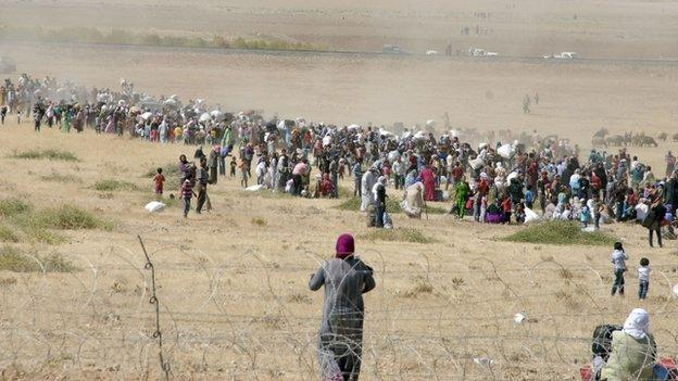 Turkey says at least 66,000 Syrians have crossed the border in 24 hours, as hundreds of Kurds head the other way to fight Islamic State militants.
