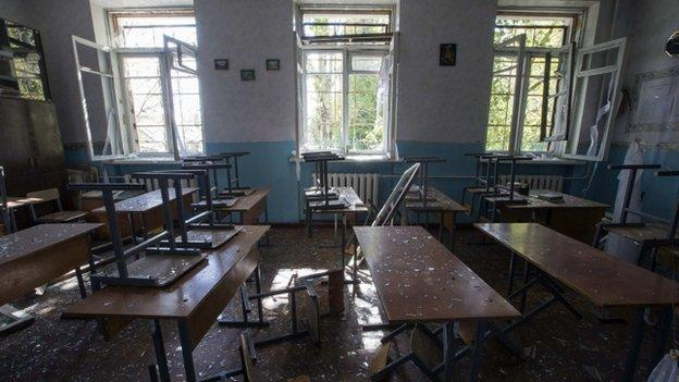 A shell blast kills four people at a school in the rebel-held Ukrainian city of Donetsk on the first day of classes, delayed because of the conflict.
