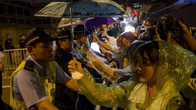 "China issues a warning against ""illegal acts"" in Hong Kong, as protesters there vow to step up their campaign if the chief executive does not resign."
