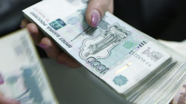 The Russian rouble weakens against the dollar after Moody's downgrades the credit rating of the nation's debt, blaming the economic damage caused by sanctions.