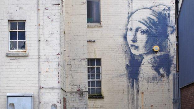 A new mural by street artist Banksy, a parody of Vermeer's Girl with a Pearl Earring, is painted on a wall in his home city of Bristol.