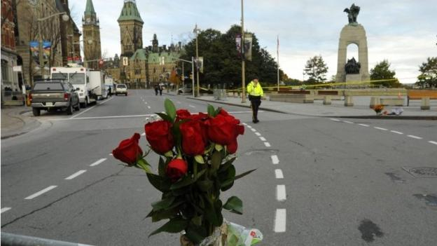 The parliament in Ottawa returns to work and gives a hero's welcome to the sergeant-at-arms who shot a gunman dead the day before.