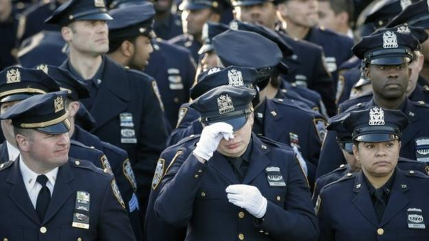 Thousands of police officers from across America attend the funeral in New York of a fellow officer shot dead after weeks of anti-police unrest.