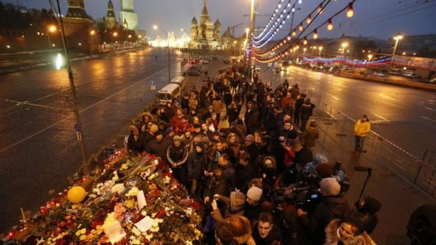 Thousands of Russians light candles and lay flowers for Boris Nemtsov, as speculation grows over the motive for the murder of President Putin's critic.