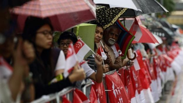 Thousands line the streets in torrential rain in Singapore to see the funeral procession of founding Prime Minister Lee Kuan Yew.