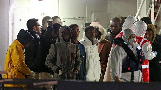 The captain and a crew member of a boat that capsized off Libya on Sunday, killing hundreds of migrants, have been arrested, Italian officials say.