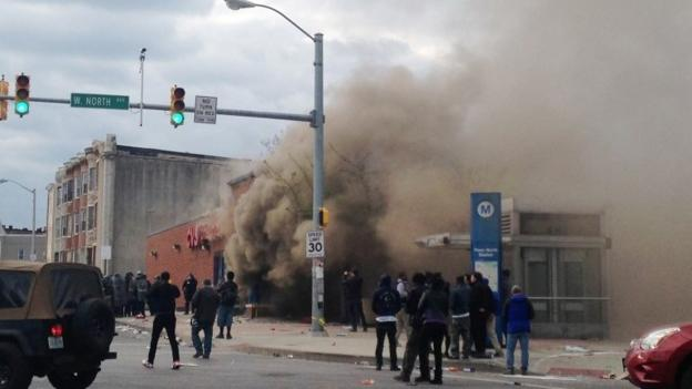 Seven officers in the US city of Baltimore are injured and a state of emergency is declared as a store and vehicles are set alight during protests.