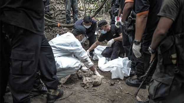Malaysia detains 12 policemen suspected of human trafficking, two of whom are said to be connected to recently discovered jungle graves.