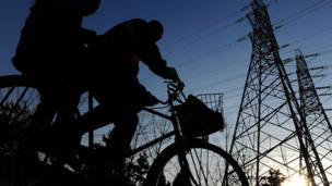 Cyclists in China pass electricity pylons (Copyright: Getty Images)