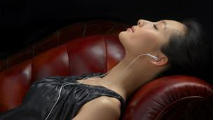 Woman reclining on sofar with iPhone earbuds in (Copyright: Thinkstock)