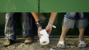 People passing toilet roll to one another (Copyright: Getty Images)