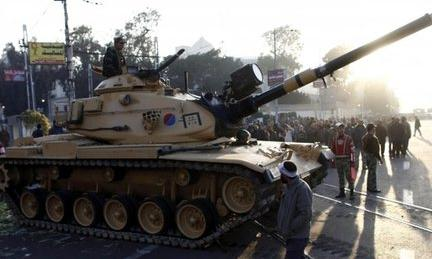 Egyptians walk past army tanks deployed near the presidential palace 6/12/12