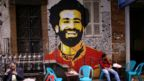 A mural of Egypt and Liverpool football star Mohamed Salah is seen as people sit outside a street coffee shop downtown in the capital of Cairo, Egypt January 16, 2018.