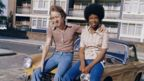A couple sit on the bonnet of an MG in London, 1970s