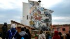 A group of students look at a street art mural on the facade of a house in Fanzara near Castellon de la Plana