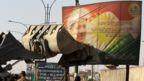 Iraqi forces use a tractor to damage a poster of Iraqi Kurdish president Massud Barzani on the southern outskirts of Kirkuk on October 16, 2017