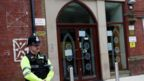 A police officer stands outside Didsbury mosque in Manchester,