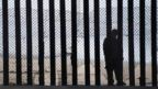A man is seen standing on the Mexico side of a border fence separating the US at Border Field State Park in San Diego, California.