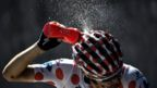 Poland's Rafal Majka, wearing the best climber's polka dot jersey, spays water on himself d