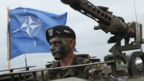 A Polish soldier sits in a tank as a Nato flag flies behind during Nato military exercises on 18 June 2015 in Zagan, Poland