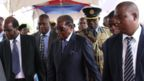 Mr Mugabe surrounded by people including one man in full uniform