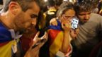 Independence supporters listen to Carles Puigdemont's speech on phones in Barcelona, 21 October