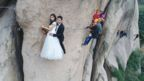 A wedding photo shoot on a cliff face with the couple in formal wear.