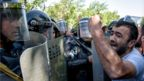 A man shouts in front of Armenian special police forces blocking a street during an opposition rally in central Yerevan