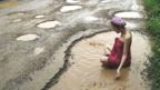 Woman bathing in pothole