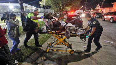 """Officials remove a man from the scene following a shooting in New Orleans"""" 9th Ward on Sunday, Nov. 22, 2015."""